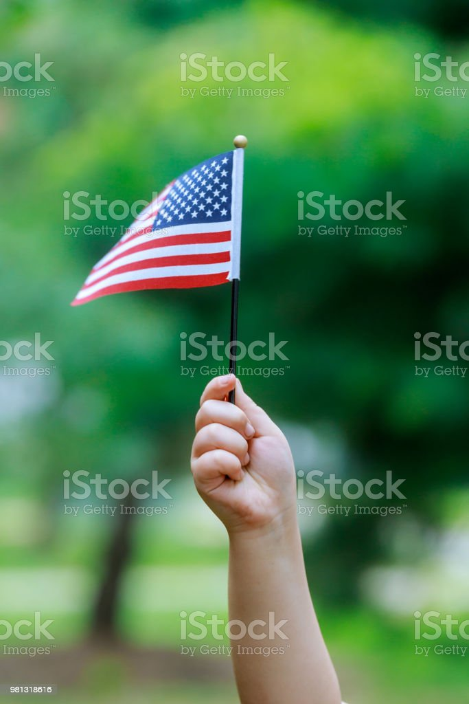 The girl holds the US flag in her hands. Close-up. stock photo