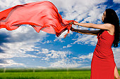 The girl in a red dress and with a red shawl flying on a wind on a green floor on a background of the blue sky with clouds