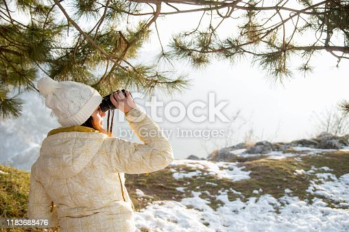 The girl in a White cap with a backpack in the winter in a forest looking through binoculars