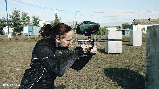 The girl in black shoots from a paintball marker on the open-air ground with gray figures. Side view. Paintball game