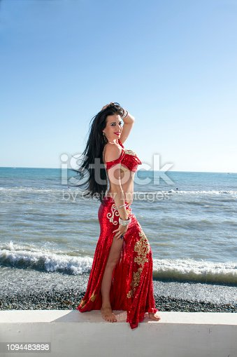 The girl in eastern clothes on the background of the sea