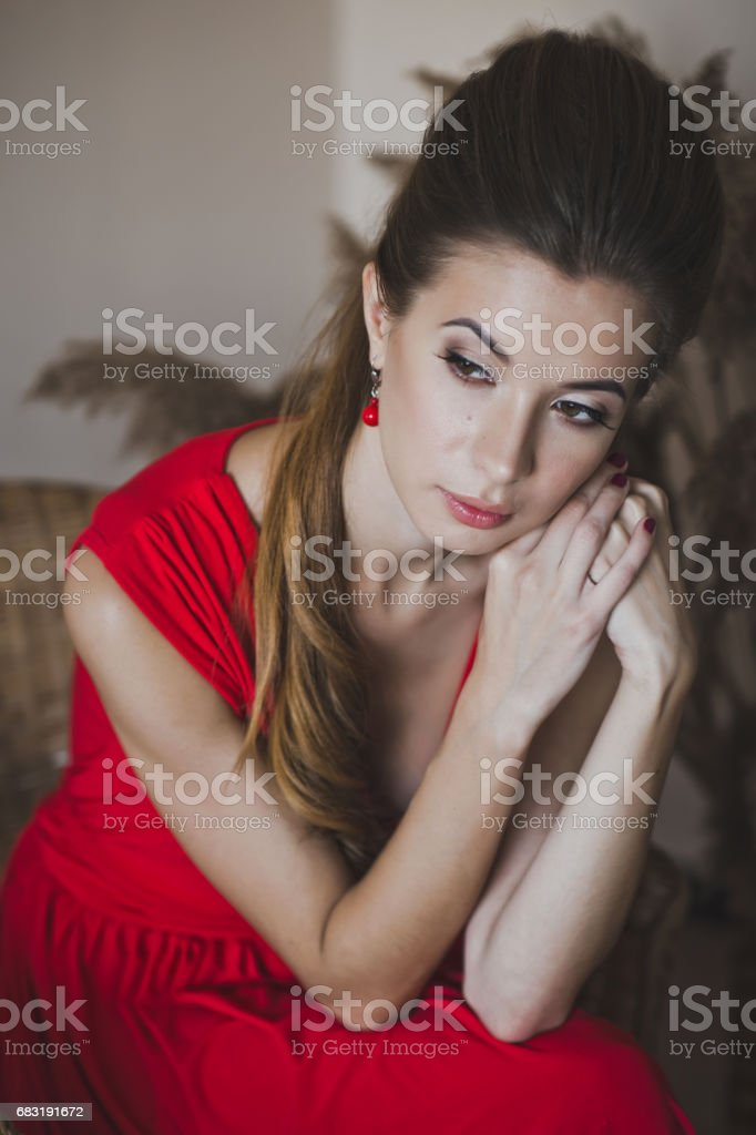 The girl in long red dress sitting in a chair 4912. 免版稅 stock photo
