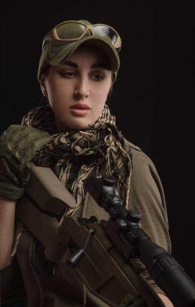 the girl in military special clothes posing with a gun in his hands on a dark background in the haze stock photo