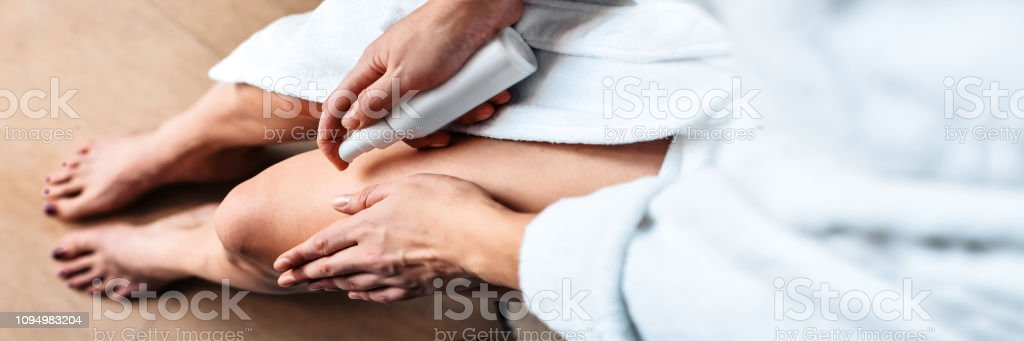 The girl in the bathroom puts anti-cellulite cream, serum on the legs and body. Body care concept. Top View. Banner - foto stock