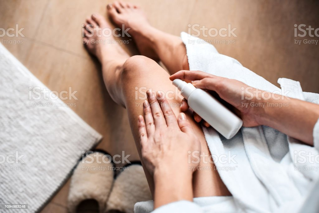 The girl in the bathroom puts anti-cellulite cream, serum on the legs and body. Body care concept. Top View - foto stock