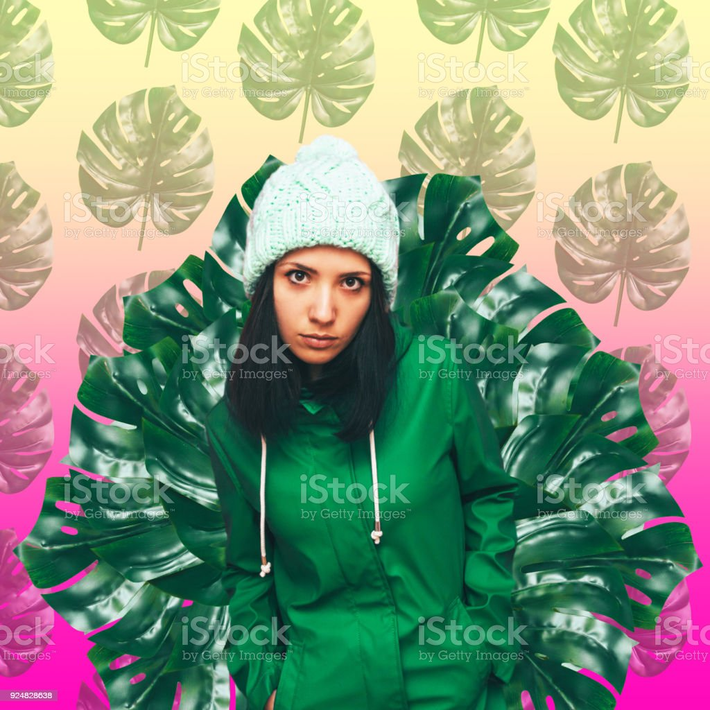 the girl in the green coat and hat on a background of palm leaves stock photo