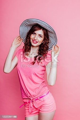girl pinup-style in a pink dress with hat with brim