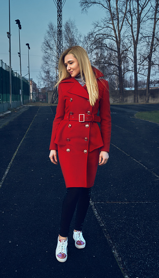The girl in the red coat stands and looks away. The girl on the opposite court. Stylish red coat. Autumn clothing