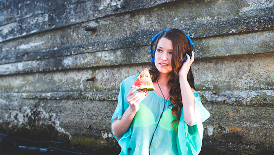 1155046257 istock photo The girl in the river in headphones with watermelon 487371132
