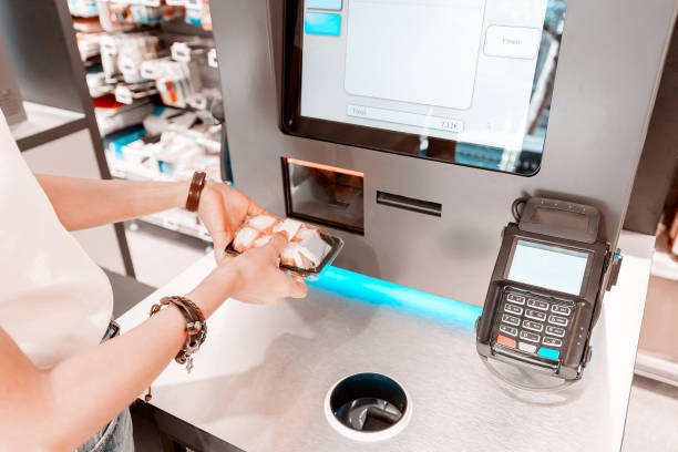 The girl in the supermarket buys sushi and makes a purchase at the checkout self-service stock photo
