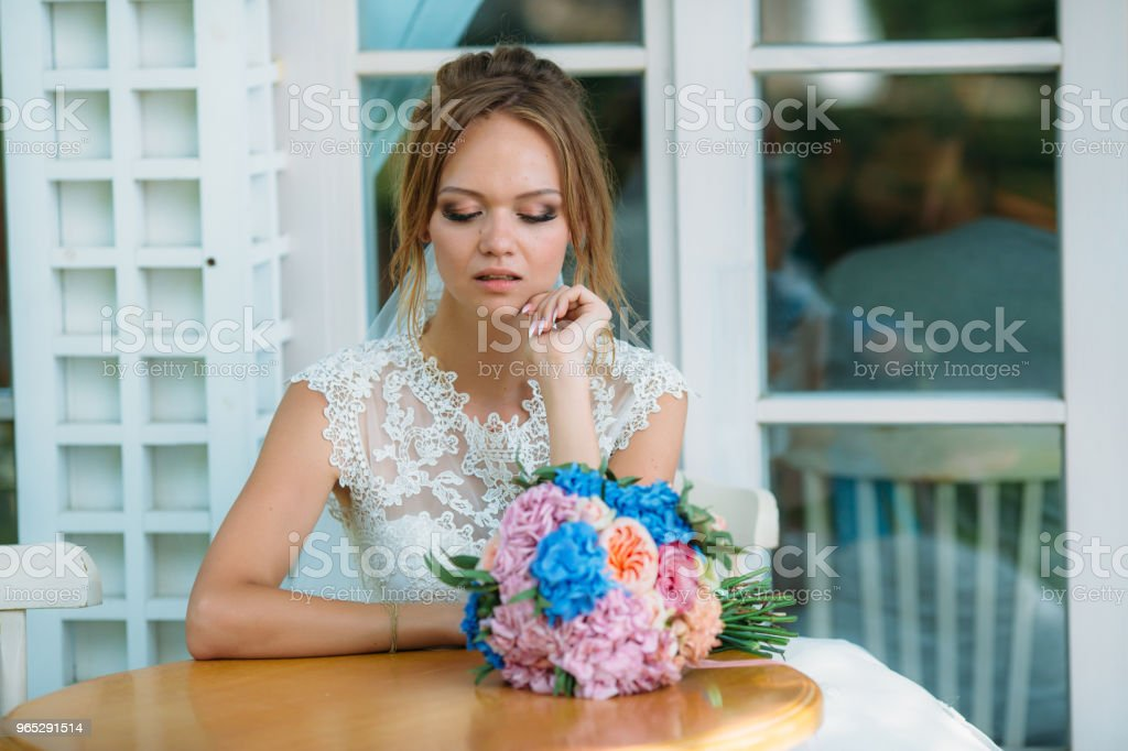 The girl in the wedding dress sits at the table alone and looks upset. The bride looks sadly at a bouquet of flowers royalty-free stock photo