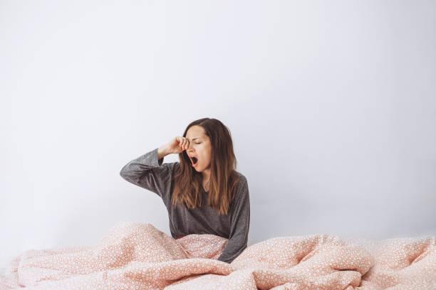 Das Mädchen liegt im Bett und gähnt – Foto