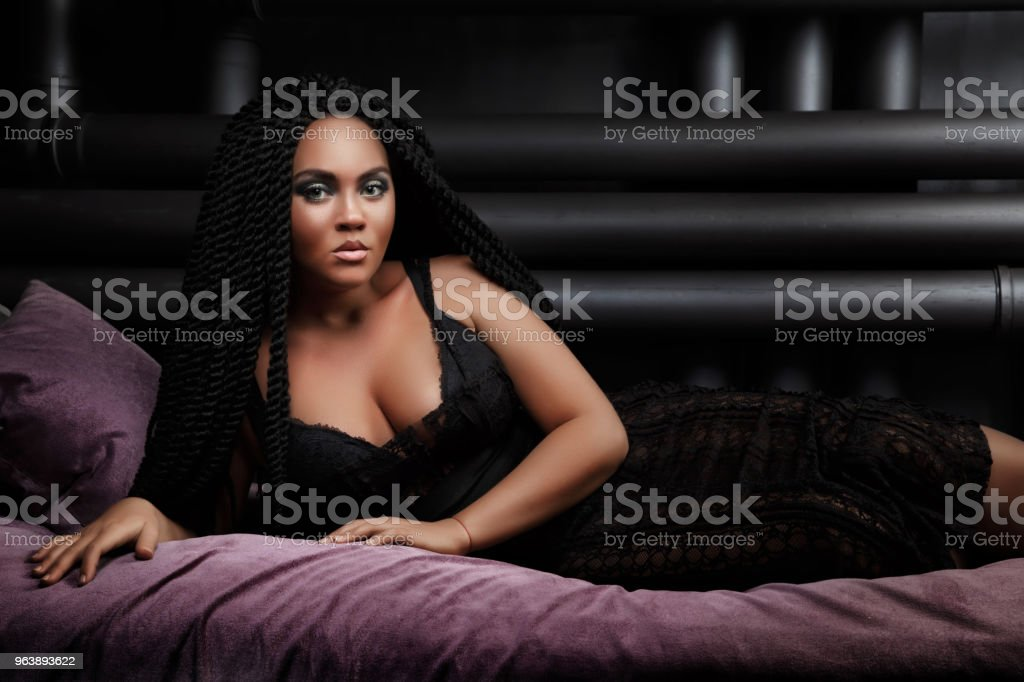The girl is lying on the bed. Stylish hairstyle, dreadlocks. Black lady. nightfall - Royalty-free Adult Stock Photo