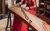 The girl is playing a guqin in a tea house in Chongqing, China.