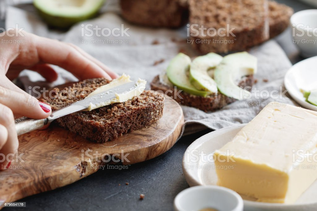 The girl is preparing toast from rye bread and butter for breakfast. stock photo