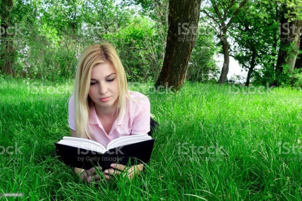 the girl is reading a book lying on the grass royalty-free stock photo