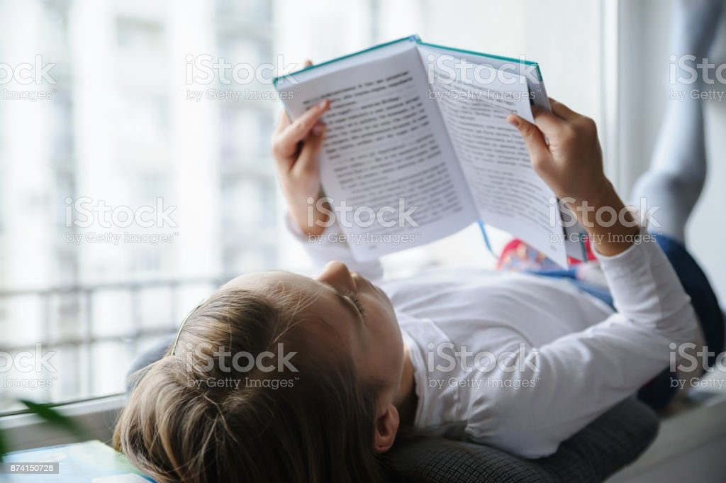 The girl is reading a book. stock photo