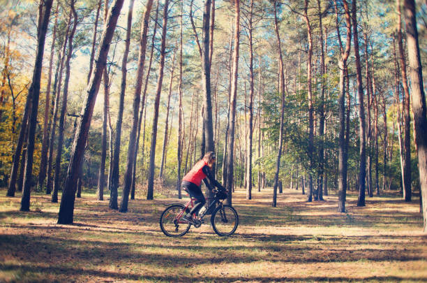 the girl is riding a bicycle through the woods stock photo