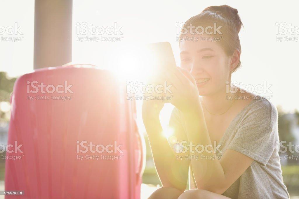 Das Mädchen sitzt auf der Straße mit ihren rosa Koffer bereit, an einem sehr sonnigen Tag im Sommer Reisen. – Foto