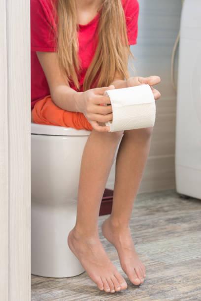 A moça está sentada no vaso sanitário com um rolo de papel higiênico nas mãos - foto de acervo