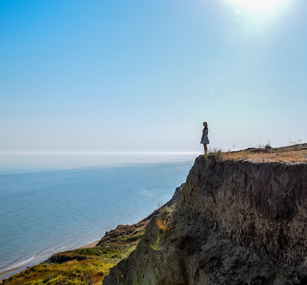 The girl is standing on a cliff near the sea