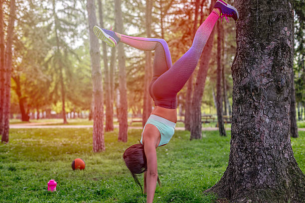 the girl is stretching on a tree stock photo