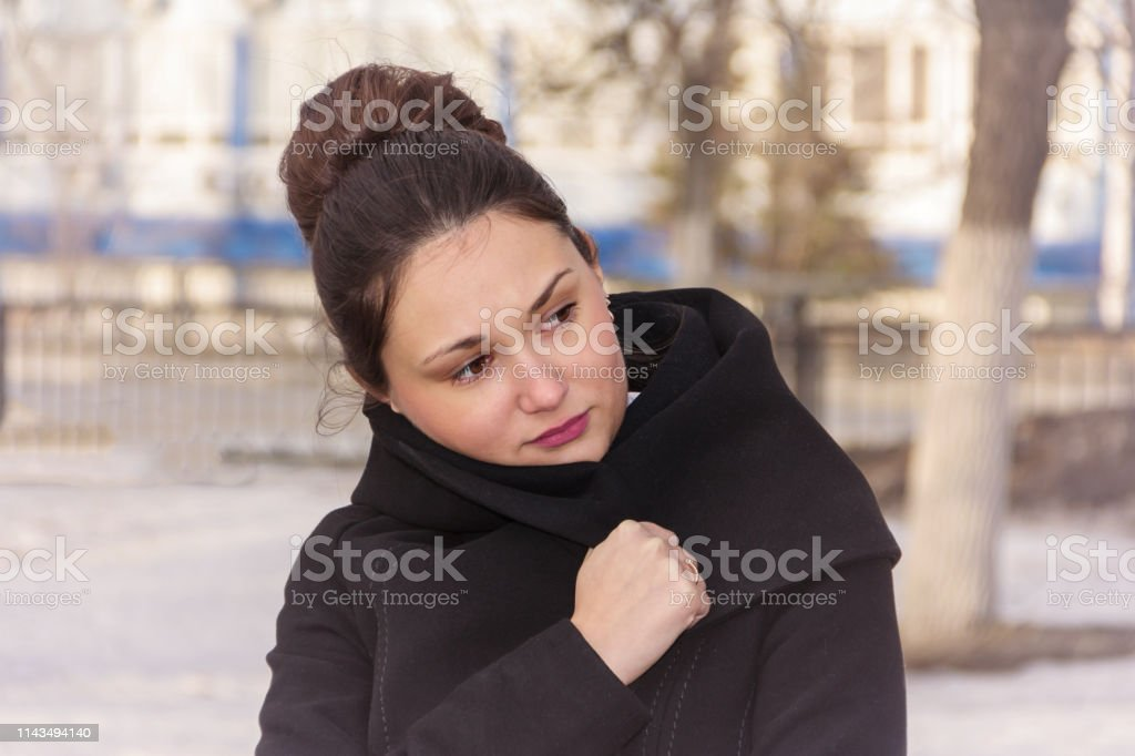 The girl is wrapped in a coat. royalty-free stock photo