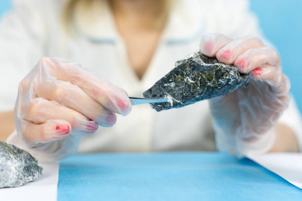 The girl laboratory technician examines samples of minerals. stock photo