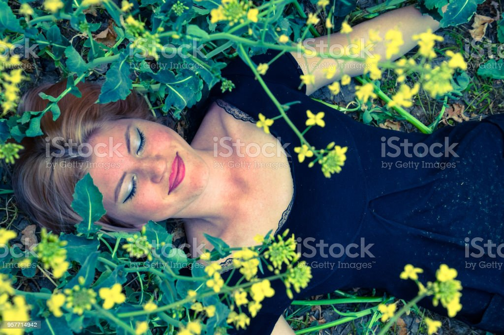 The girl lay down on the ground in the field of flowering rape. The...