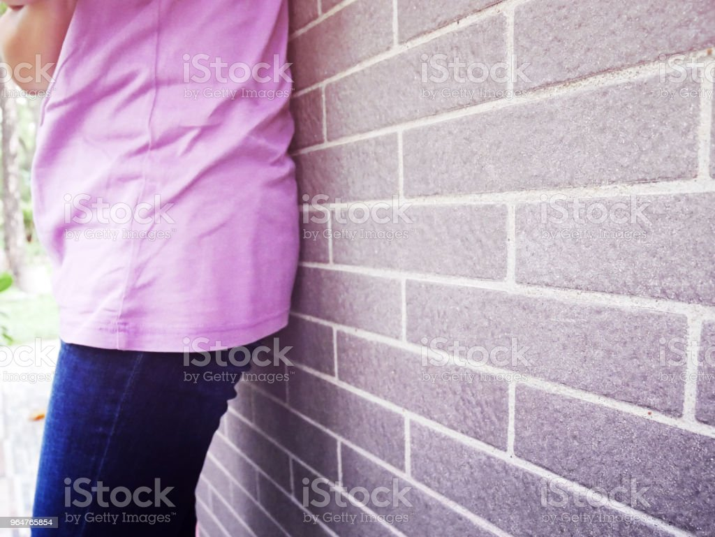 The girl leaning against the wall waiting for her lover to come. royalty-free stock photo
