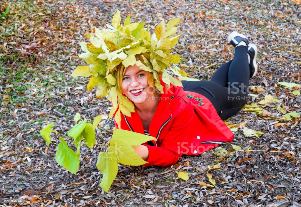The girl lies in the autumn fallen foliage. Girl in a red jacket with a wreath of yellow autumn leaves. The Queen of Autumn. Miss autumn. Autumn Walk. stock photo