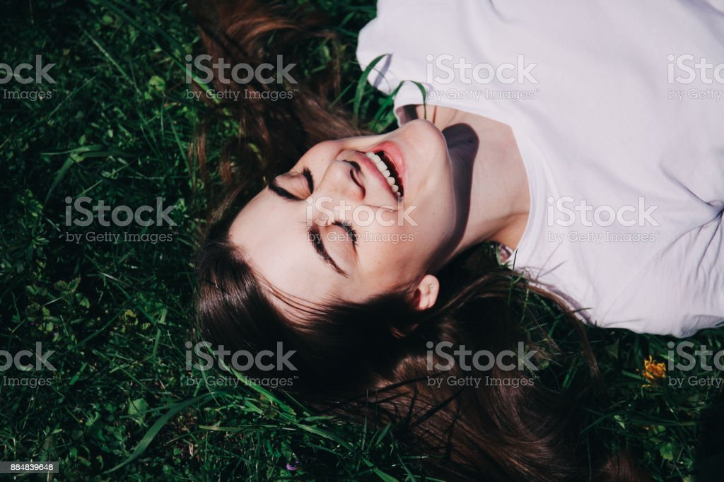 The girl lies on the green grass. stock photo
