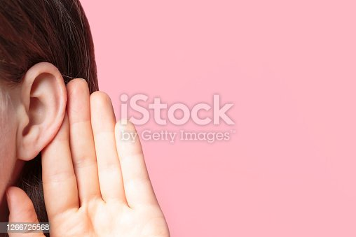 The girl listens attentively with her palm to her ear close-up on a pink background