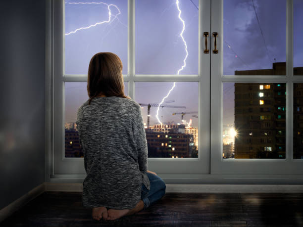The girl looks through the window at the lightning. Thunderstorm in the city stock photo