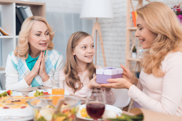 The girl makes a gift to mom and grandmother on March 8. The girl makes a gift to mom and grandmother on March 8. They are sitting at the festive table. group of friends giving gifts to the birthday girl stock pictures, royalty-free photos & images