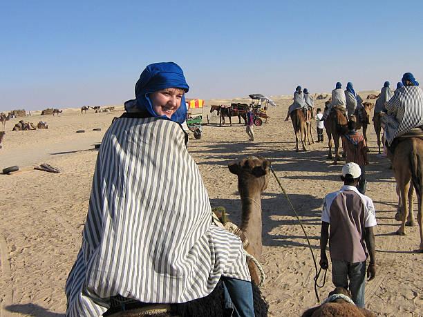 das mädchen auf einem kamel - urlaub in tunesien stock-fotos und bilder