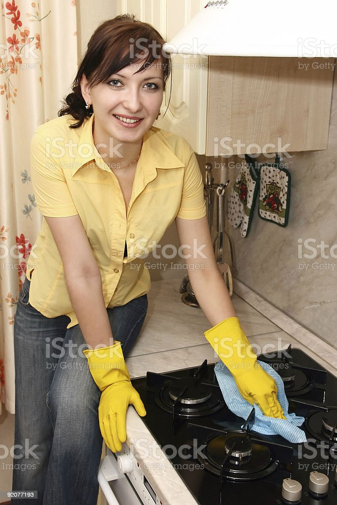 The girl on kitchen wipes a gas cooker royalty-free stock photo