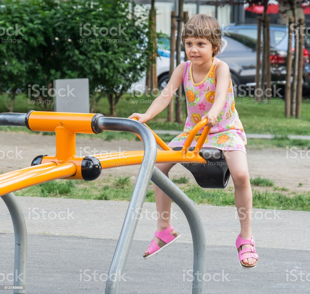 The girl on teeter-totter in playground stock photo