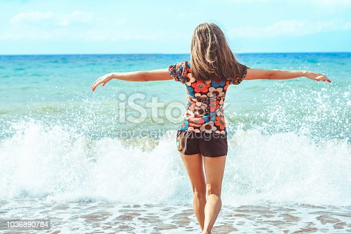 a young girl in shorts stands with her back against the background of big waves