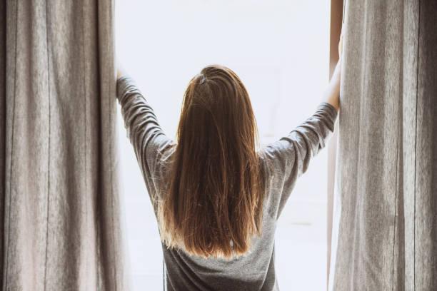 Das Mädchen öffnet die Vorhänge – Foto