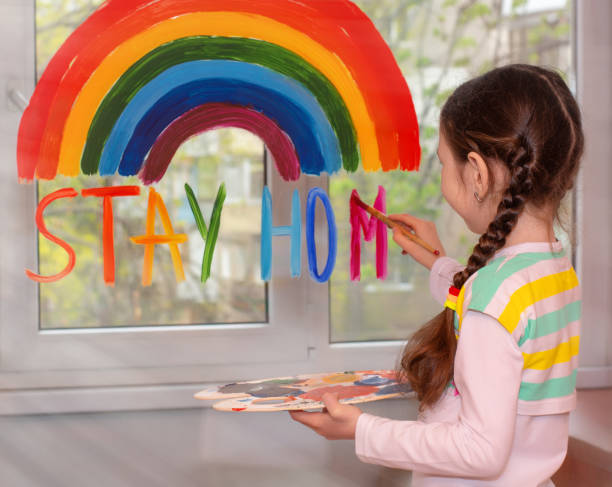 """the girl paints a rainbow on the window and writes the text """"stay home"""" in multicolored letters.quarantine fun.flash mob society community on self-isolation stay home!let's all be well. - prevenzione delle malattie foto e immagini stock"""