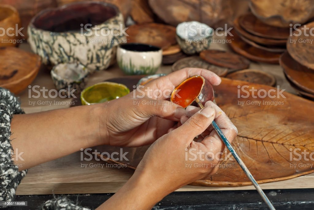 The girl paints pottery. Handmade products on the table at home...