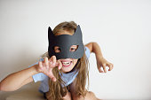 The girl plays in a self-made mask of black cat for Halloween