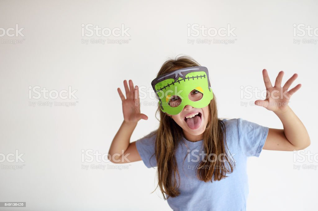 The girl plays in a self-made mask of Frankenstein stock photo