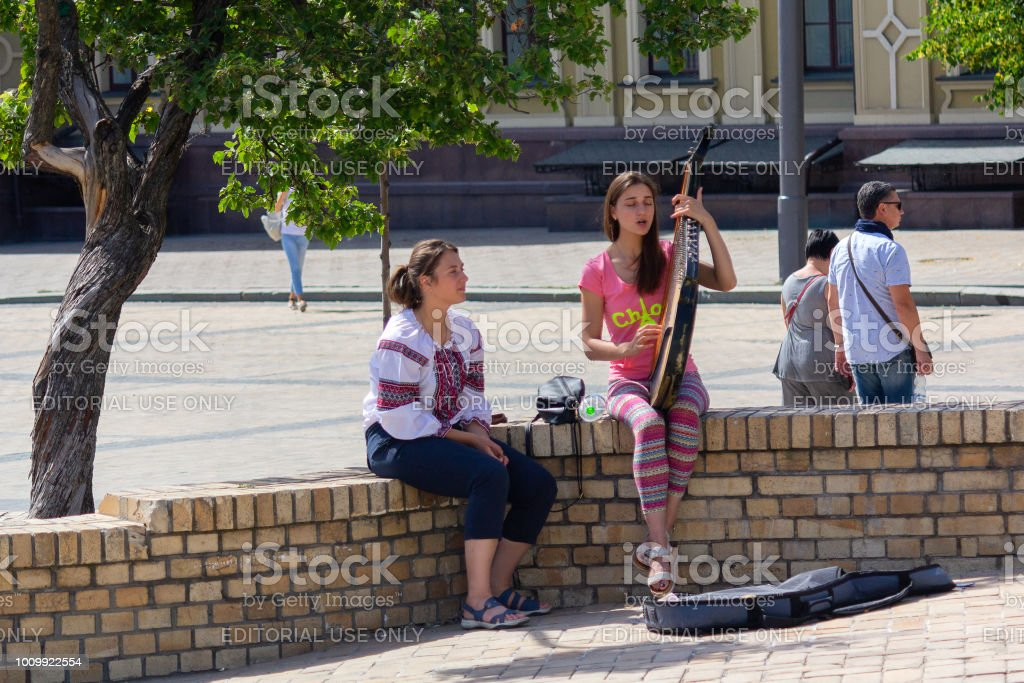 The girl plays the folk instrument of the bandura on the town square стоковое фото