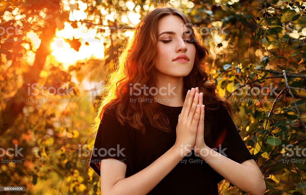 The girl prays in nature eyes closed. stock photo