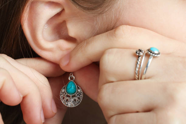 The girl puts on a earring with a turquoise stone on her ear stock photo