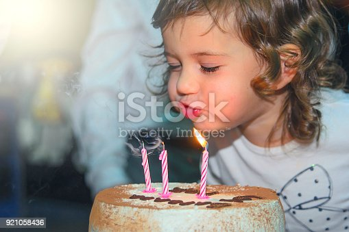 The girl puts out the candles on a birthday cake