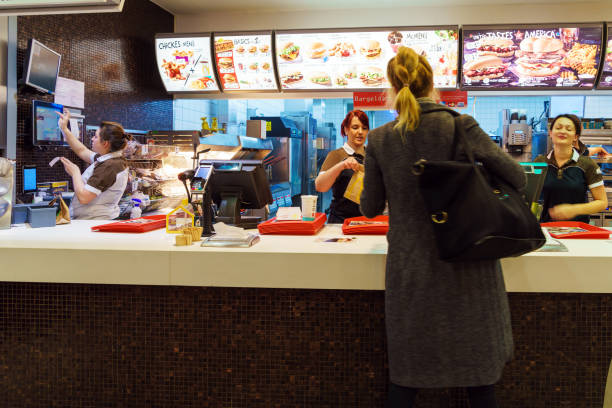 The girl receives an order in the interior of the McDonald's, Munich, Germany stock photo