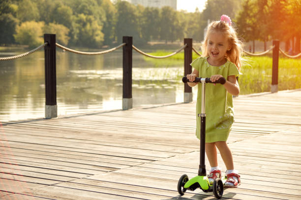 The girl rides a scooter in the park near the water. Happy child, children's entertainment, active child stock photo